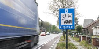 Un camión pasa al lado de una señal que advierte de un peaje para camiones.