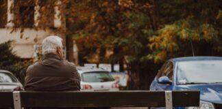 Un hombre mayor sentado en un banco en otoño.