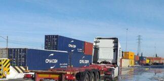 Un camión transporta un contenedor en una terminal ferroviaria.